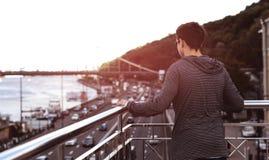Hombre joven en un puente en una ciudad grande Imágenes de archivo libres de regalías