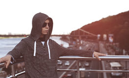Hombre joven en un puente en una ciudad grande Foto de archivo libre de regalías