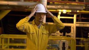 Hombre joven en un uniforme amarillo, vidrios y casco del trabajo en planta del ambiente industrial, de la plataforma petrolera o almacen de video