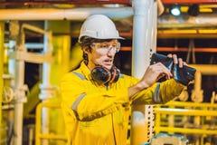Hombre joven en un uniforme amarillo, vidrios y casco del trabajo en planta del ambiente industrial, de la plataforma petrolera o imagen de archivo libre de regalías