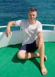 Hombre joven en un yate de la tarjeta Imagenes de archivo