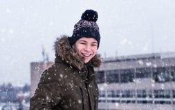 Hombre joven en una calle de la ciudad durante nevadas Foto de archivo