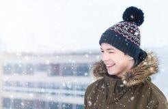 Hombre joven en una calle de la ciudad durante nevadas Imagen de archivo libre de regalías