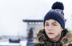 Hombre joven en una calle de la ciudad durante nevadas Fotos de archivo libres de regalías