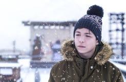 Hombre joven en una calle de la ciudad durante nevadas Fotografía de archivo libre de regalías