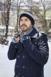 Hombre joven en una capa cubierta con nieve Foto de archivo libre de regalías