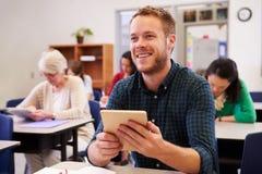 Hombre joven en una clase de la enseñanza para adultos que mira para arriba el tablero fotos de archivo libres de regalías