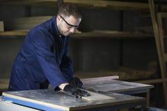 Hombre joven en una fábrica de los muebles que corta los pedazos de madera para el sofá foto de archivo libre de regalías