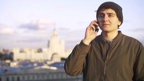 Hombre joven en una gorrita tejida en un teléfono en un tejado almacen de video