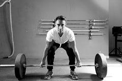 Hombre joven en una sesión del levantamiento de pesas - entrenamiento del crossfit Fotos de archivo