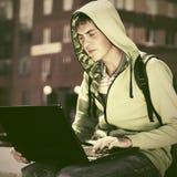 Hombre joven en una sudadera con capucha usando el ordenador portátil Foto de archivo libre de regalías