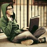 Hombre joven en una sudadera con capucha usando el ordenador portátil en calle de la ciudad Fotografía de archivo