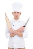 Hombre joven en uniforme del cocinero con el rodillo de madera de la hornada y el kni Imágenes de archivo libres de regalías
