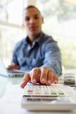 Hombre joven en usar la calculadora en casa Imagenes de archivo