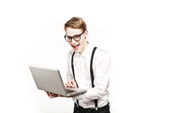 Hombre joven en vidrios con el ordenador portátil con la emoción Foto de archivo