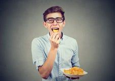 Hombre joven en vidrios que come las patatas fritas Foto de archivo