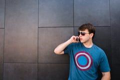 Hombre joven en vidrios que habla en un teléfono móvil y que mira de lado a lado contra una pared gris Fotografía de archivo libre de regalías