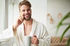 Hombre joven encantado que habla en el teléfono por mañana Imagenes de archivo