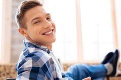 Hombre joven encantado que se relaja y que sonríe Fotografía de archivo libre de regalías