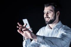 Hombre joven encantado que usa su dispositivo Imágenes de archivo libres de regalías