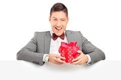 Hombre joven encantador que lleva a cabo un presente y que presenta detrás del panel Imagen de archivo
