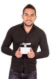 Hombre joven encantador que sostiene una caja de regalo Foto de archivo