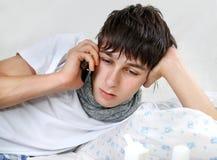 Hombre joven enfermo con el teléfono Fotos de archivo libres de regalías