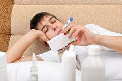 Hombre joven enfermo con el termómetro Fotografía de archivo libre de regalías