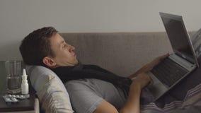 Hombre joven enfermo en la cama que trabaja en el cuaderno Las píldoras y las medicaciones de la abundancia están en la mesita de almacen de video
