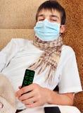 Hombre joven enfermo en máscara de la gripe Imagenes de archivo