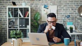 Hombre joven enfermo usando el ordenador portátil en oficina entonces que estornuda limpiando la nariz con el tejido almacen de video