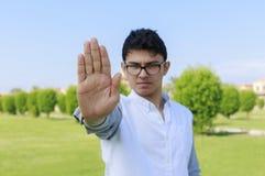 Hombre joven enojado con la chamusquina de la parada a mano Imagen de archivo