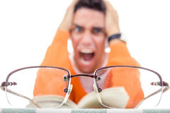 Hombre joven enojado con los vidrios en libro de lectura del suéter Imagen de archivo