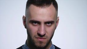 Hombre joven enojado en el fondo blanco Cierre para arriba Cámara lenta metrajes