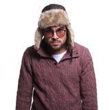 Hombre joven enojado en ropa del invierno y sombrero de piel Imagen de archivo