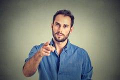 Hombre joven enojado que señala el finger en usted gesto de la cámara Foto de archivo libre de regalías