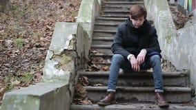 Hombre joven enojado que siente enfermo y cansado de la vida, puños de apretón desamparadamente metrajes