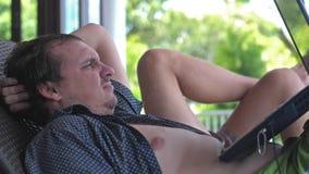 Hombre joven enojado que usa el ordenador portátil en balcón en el centro turístico el vacaciones Cámara lenta 3840x2160 metrajes