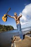 Hombre joven entusiástico con la guitarra que coloca Lakesi Imágenes de archivo libres de regalías