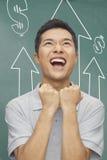 Hombre joven entusiasta con los brazos aumentados, delante de la pizarra con las muestras y las flechas del dinero Imágenes de archivo libres de regalías
