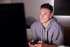 Hombre joven enviciado al juego video en casa Foto de archivo