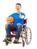 Hombre joven esperanzado que se sienta en una silla de ruedas con un baloncesto Imagen de archivo libre de regalías