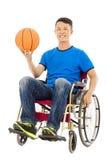 Hombre joven esperanzado que se sienta en una silla de ruedas con un baloncesto Fotografía de archivo