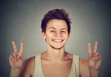 Hombre joven, estudiante hermoso que soporta la victoria de la paz, muestra dos Imagenes de archivo