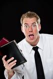 Hombre joven exaltado que sostiene las biblias Fotos de archivo libres de regalías