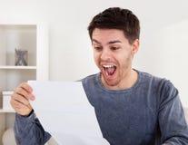 Hombre joven exultante que anima buenas noticias Imagen de archivo