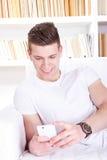 Hombre joven feliz casual que envía el mensaje en el teléfono móvil Imagenes de archivo