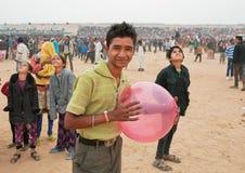 Hombre joven feliz con el globo que camina en la muchedumbre de gente imagen de archivo