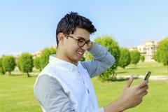 Hombre joven feliz con el teléfono elegante a disposición, al aire libre Imagen de archivo