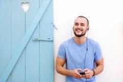 Hombre joven feliz con la barba que escucha la música en el teléfono móvil Imagen de archivo libre de regalías